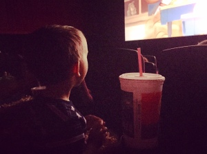 """watching """"the peanuts"""" on the big screen! he wanted to sit in his own seat all by himself!"""